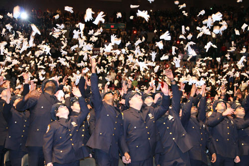 New York City's Police Academy graduates celebrate by throwing their gloves in the air. Family and friends of the 1,359 rookies fill Madison Square Garden in the December 2006 ceremony. Photo by Pat Arnow