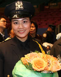 New NYPD graudate after the ceremony at Madison Square Garden, December 2006. She was the first in her family (who were all there) to become a police officer. Her husband brought the flowers to the ceremony for her. (Arnow photo)