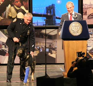 BOUND ONLY BY BARGAINING LAWS: With a panoramic backdrop to match his list of accomplishments, Mayor Bloomberg didn't fear being upstaged by a hero police dog (Ranger, accompanied by Police Officer Neal Campbell) as he delivered his State of the City address. (Arnow photo)