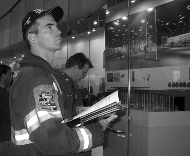Firefighter Parick McCarvill looks at World Trade Center memorial designs. Photo by Pat Arnow.