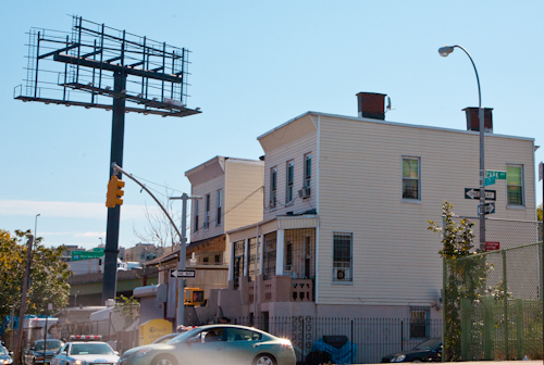 Houses and billboard frame abut the Cross-Bronx Expressway at 175th St. and Park Ave., Bathgate neighborhood, Bronx, NY. Photo by Pat Arnow