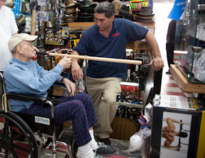 Irv Fishman examines a stickball bat in Frank's Sport Shop, Tremont Ave., Bronx. Photo by Pat Arnow.