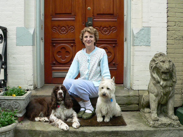 A Pittsburgh woman stoops sits with her dogs and a stone lion. Photo by Pat Arnow